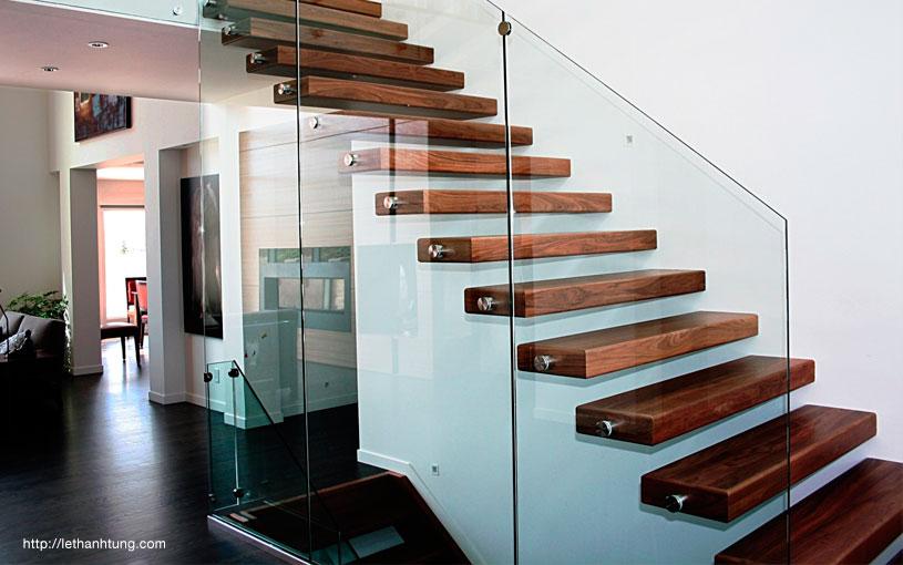 escaleras de cristal de peldaos de madera fina con muros y barandas de cristal